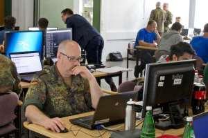 Viele, zum Teil in Tarnuniformen gekleidete Menschen sitzen in einem Raum an Computern.