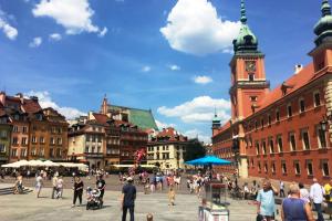 Renovierte mehrstöckige Altbauten und ein Klinker-Prachtbau begrenzen einen sommerlich anmutenden Platz mit Menschen darauf, überspannt von einem blauen Himmel mit vereinzelten Kumuluswolken.