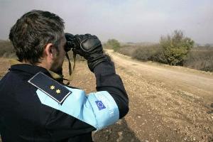 """Ein uniformierter Polizist blickt durch ein Fernglas in eine steppenartige Landschaft; er trägt eine blaue Armbinde mit der Aufschrift """"FRONTEX""""."""