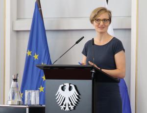 Dr. Franziska Brantner steht an einem Pult mit dem Bundesadler darauf und spricht in ein Mikrofon; im Hintergrund stehen die Flaggen der EU und Finnlands.