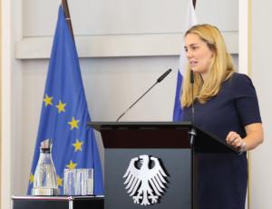 Victoria Wieninger steht an einem Pult mit dem Bundesadler darauf und spricht in ein Mikrofon; im Hintergrund stehen die Flaggen der EU und Finnlands.