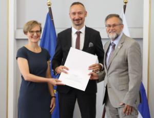 Sven Kahle steht mit einer Urkunde in den Händen zwischen Dr. Franziska Brantner und Wolfgang Rudischhauser