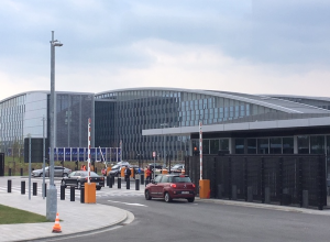 Im Hintergrund ragt das NATO-Hauptquartier auf; im Vordergrund steht ein Wachgebäude mit einer Schranke, vor der ein Auto angehalten hat.