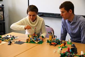 Eine Frau und ein Mann sitzen an einem Tisch und erbauen etwas aus Lego.