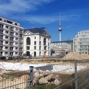 Das Bild zeigt eine Baustelle, die von mehreren Gebäuden umsäumt wird; im Hintergrund ragt der Berliner Fernsehturm auf.