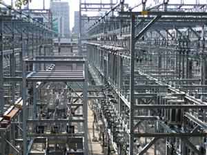 Das Bild zeigt ein unübersichtliches, fluchtpunktartig zusammenlaufendes Gewirr von Metallstreben, Transformatoren, Isolatoren und Stromleitungen in einem Umspannwerk.