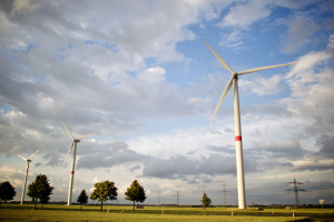In einer flachen Landschaft mit Rapsfeldern und wenigen kleinen Laubbäumen stehen drei Windräder zur Stromerzeugung und im Hintergrund eine Reihe Strommasten.