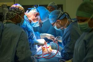 Mehrere mit Operationskleidung und Mundschutz verhüllte Ärzte beugen sich mit Operationswerkzeug über einen verdeckt liegenden Patienten.