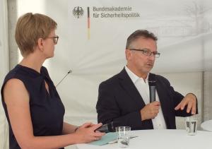 Die Journalistin Ulrike Scheffer und der Präsident der BAKS Dr. Karl-Heinz Kamp stehen nebeneinander an einem Stehtisch; im Hintergrund hängt ein Banner der BAKS, und Kamp spricht in ein Mikrofon in seiner Hand.