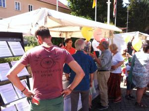 An einem Informationsstand der BAKS stehen zahlreiche Menschen; links im Bild ragt ein Ständer mit mehreren ausgelegten Papierstapeln auf.