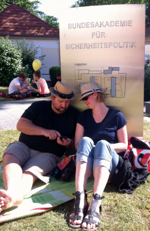Ein (von links) Mann und eine Frau sitzen auf einer Wiese angelehnt an ein großes Metallschild mit dem Namen der BAKS darauf und schauen auf ein Mobiltelefon in der Hand des Manns; im Hintergrund sitzen weitere Menschen mit einem Luftballon.