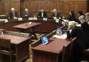 In einem Ausschusssaal des britischen Parlaments befinden sich Ausschussmitglieder in einer Videokonferenz mit BAKS-Präsident Karl-Heinz Kamp, dessen Bild auf mehreren Monitoren übertragen wird.