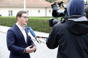 Dr. Sven Herpig gibt vor dem Gebäude der BAKS einem Fernsehteam ein Interview; rechts im Bild stehen die Kamera und ein Kameramann; von rechts außerhalb des Bildes wird ihm ein Mikrofon hingehalten.