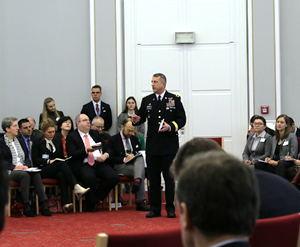 A military officer is standing among an audience of several both uniformed and business-dressed people and speaks into a microphone.
