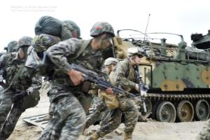 In Tarnanzügen gekleidete Soldaten verschiedener Staaten mit Kampfausrüstung rennen an einem Panzerfahrzeug vorbei.