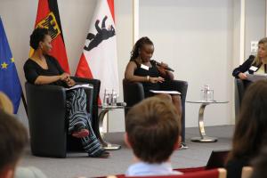 Drei Frauen sitzen auf einem Podium und sprechen miteinander vor einem Publikum.