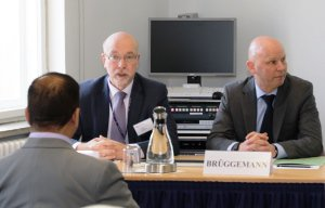 Die Referenten der BAKS Oberstleutnant Volker Berding und Dr. Ulf Brüggemann sprechen hinter einem Tisch mit Unterlagen sitzend zu den Angehörigen der jordanischen Delegation.