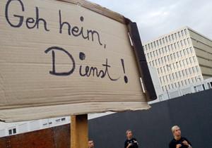 """Das Bild zeigt ein Pappschild mit der Aufschrift """"Geh heim, Dienst"""" vor dem BND-Neubau in Berlin."""