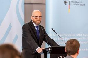 Staatssekretär Dr. Peter Tauber steht an einem Rednerpult und spricht in ein Mikrofon; im Hintergrund steht eine hellblaue Pressewand mit der Aufschrift BAKS.