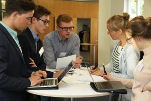 Eine gruppe junger Menschen steht um einen Tisch und diskutiert; auf dem Tisch stehen mehrere Notebooks.