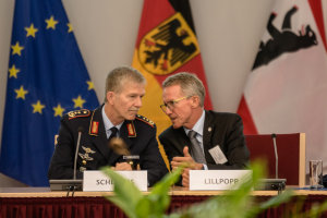 Zwei Männer, einer im Anzug und einer in Unifrom, sitzen an einem Tisch.
