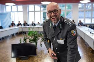 Ein lachender Mann in Uniform beugt sich über einen Tisch; im Hintergrund sitzen Menschen um ein Tischkarree.