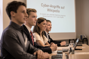 """Vier junge Menschen sitzen an einem Tisch; im Hintergrund wird eine Präsentation mit dem Titel """"Cyberangriffe auf Wikipedia""""  auf eine Leinwand projiziert."""