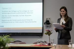 Eine junge Frau steht neben einem Whiteboard und trägt Präsentationsinhalte vor.