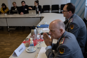 Zwei Offiziere in Uniform, im Vordergrund ein General, sitzen an einem Tisch und hören einem Sprechenden außerhalb des Bildes zu.