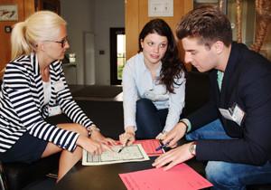 Zwei Studentinnen und ein Student diskutieren über Arbeitsnotizen.