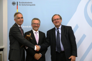 Drei Männer stehen vor einer Pressewand und geben sich die Hände