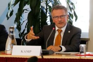 BAKS-Präsident Kamp sitzt an einem Tisch und spricht gestikulierend in ein Mikrofon.