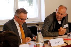 Studiendirektor Torsten Schreier sitzt neben BAKS-Präsident Kamp an einem Tisch und spricht zu ihm herüber.