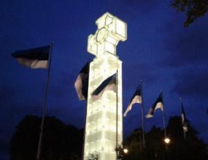 Eine Kreuzskulptur vor Nachtthimmel, dahinter wehen mehrere Flaggen im Wind.