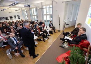 Aufnahme des Veranstaltungsraums, während ein Teilnehmer aus dem Publikum mit den Referenten auf dem Podium diskutiert