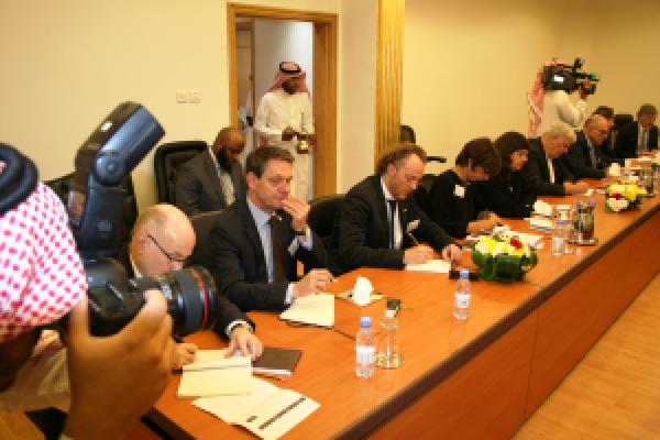 Zahlreiche geschäftlich gekleidete Menschen sitzen an einem Konferenztisch und werden von saudi-arabsich gekleideten Menschen fotografiert und gefilmt.