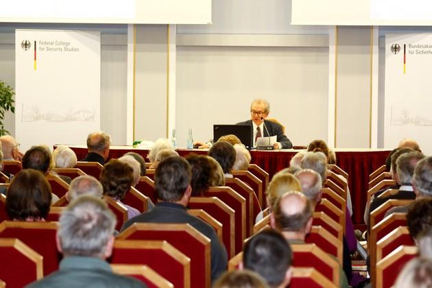 Ein Herr sitzt vor Publikum und liest vor