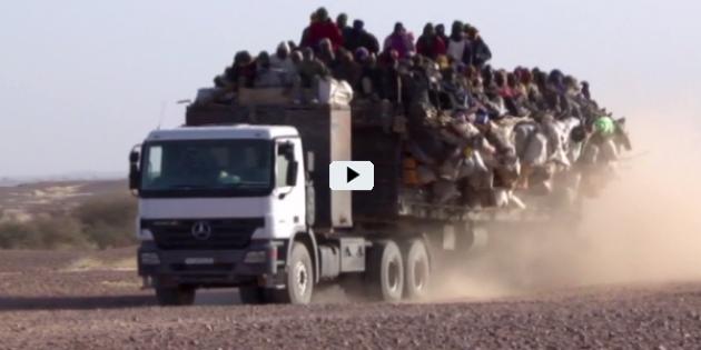 Ein Lkw in der Wüste mit offener Ladefläche, auf der sich zahlreiche Menschen drängen