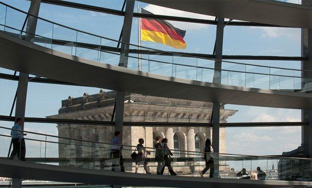 In der Kuppel des Reichstagsgebäudes laufen Menschen die spiralförmige Rampe entlang; außerhalb ist einer der Ecktürme mit einer wehenden Deutschlandflagge erkennbar.