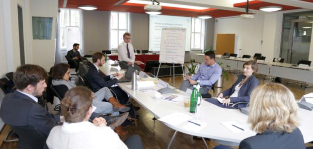 Zahlreiche junge Menschen sitzen locker um einen Konferenztisch und diskutieren miteinander.