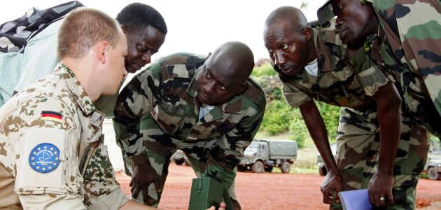 a German EUTM Mali soldier, supported by an interpreter, teaches a group of Malian soldiers how to use a metal detector