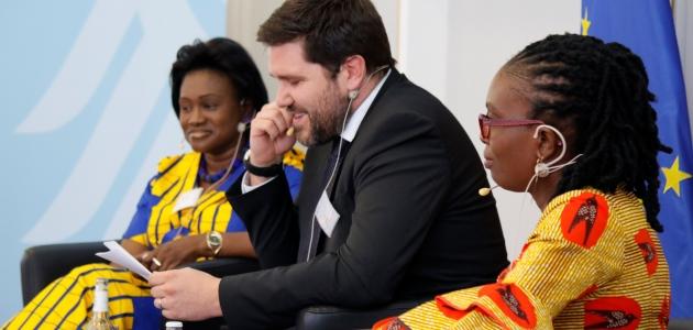 Zwei traditionell afrikanisch gekleidete Frauen und ein geschäftlich gekleideter Mann, jeweils mit Ohrbügelmikrofonen, sitzen gemeinsam auf einem Podium; links ragt eine Bundesadlerschwinge ins Bild, rechts die Europaflagge.