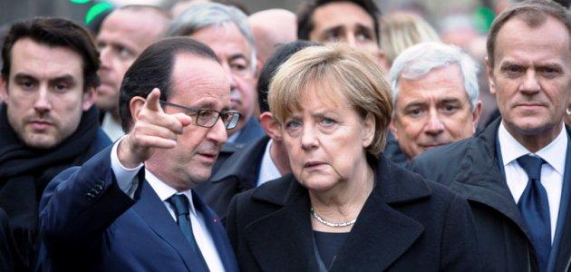 Frankreichs Präsident Francois Hollande und Deutschlands Bundeskanzlerin Angela Merkel stehen gemeinsam mit EU-Rats Präsident Donald Tusk beim Solidaritätsmarsch am 14. Januar 2015 für die Opfer der Anschläge auf das Satiremagazin Charlie Hebdo