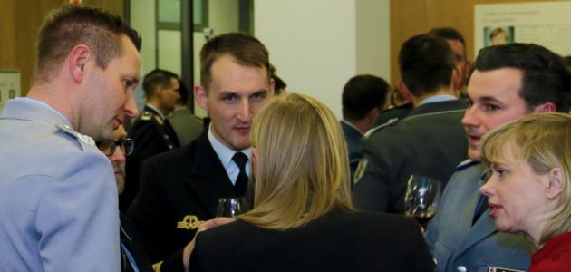 Mehrere Personen in Anzügen und Uniform stehen beieinander und unterhalten sich.