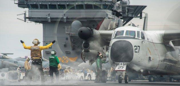Ein Flugzeug der US-Marine wird auf dem Deck eines US-Flugzeugträgers durch Deckspersonal eingewiesen.