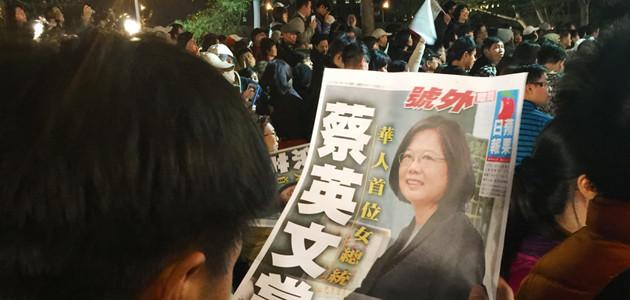 Ein Mann blickt am Tag der taiwanesischen Wahl auf eine Zeitung, die Tsai Ing-wen abbildet, die Spitzenkandidatin der DPP bei den Präsidentschaftswahlen. Im Hintergrund stehen Menschen mit Fahnen.