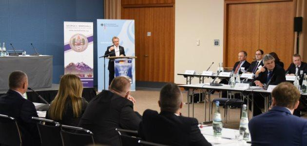 An einem rechtwinkligen Konferenztisch sitzen zahlreiche geschäftlich gekleidete Menschen; links im Bild steht ein Mann an einem Rednerpult und spricht.