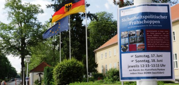 """Vor dem Haus Berlin der BAKS wehen die Flaggen der EU, Deutschlands und Berlins; an einem Laternenmast recht hängt ein Plakat mit der Aufschrift \""""Sicherheitspolitischer Frühschoppen\""""."""