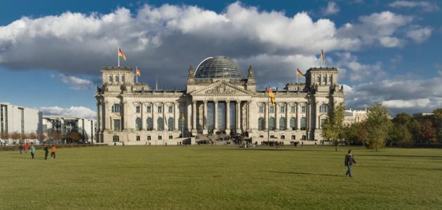 Das Foto zeigt das Plenargebäude des Deutschen Bundestages von Westen; links ist das Paul-Löbe-Haus zu erkennen, rechts Bäume des Großen Tiergartens.