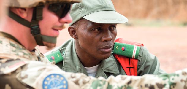 Ein deutscher Soldat zeigt auf etwas; ein nah bei ihm stehender malischer Soldat blickt in diue betreffende Richtung.